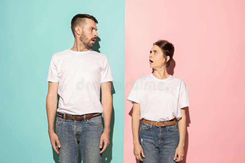 dundersuccé Tvivelaktiga eftertänksamma par med fundersamt uttrycksdanandeval mot rosa bakgrund fotografering för bildbyråer