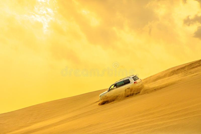 Dune Bashing sunset. Dune Bashing at sunset sky near Qatar and Saudi Arabia. Khor Al Udeid, Persian Gulf, Middle East. Inland sea is a major tourist destination royalty free stock photo