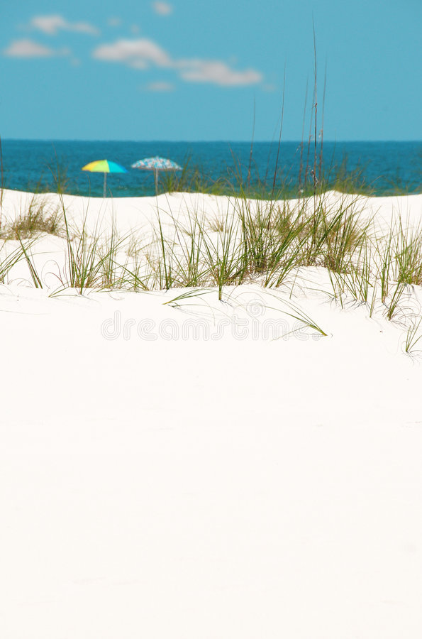 Dune de sable avec des parapluies dans la distance images stock