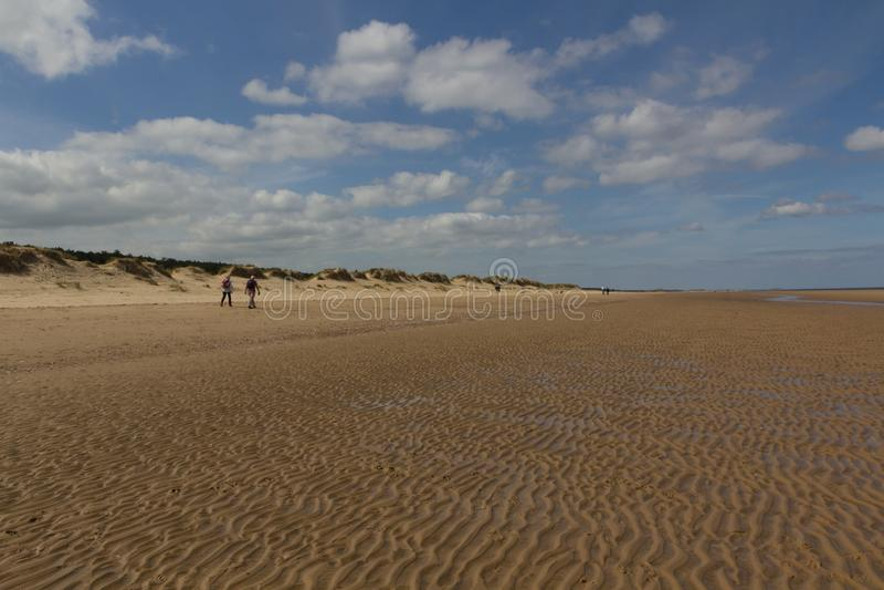 Dunes et personnes de sable marchant sur la plage à la Wells-prochain-le-mer image stock