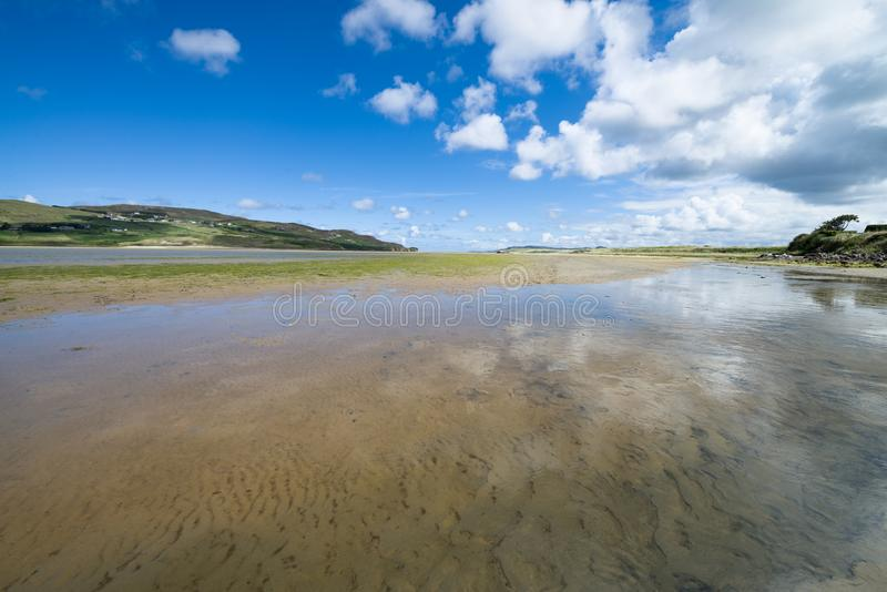 Dunfanaghy Bay at low tide in Donegal, Ireland. White sand and blue sky with clouds at Dunfanaghy beach, a typical irish beach on royalty free stock photos