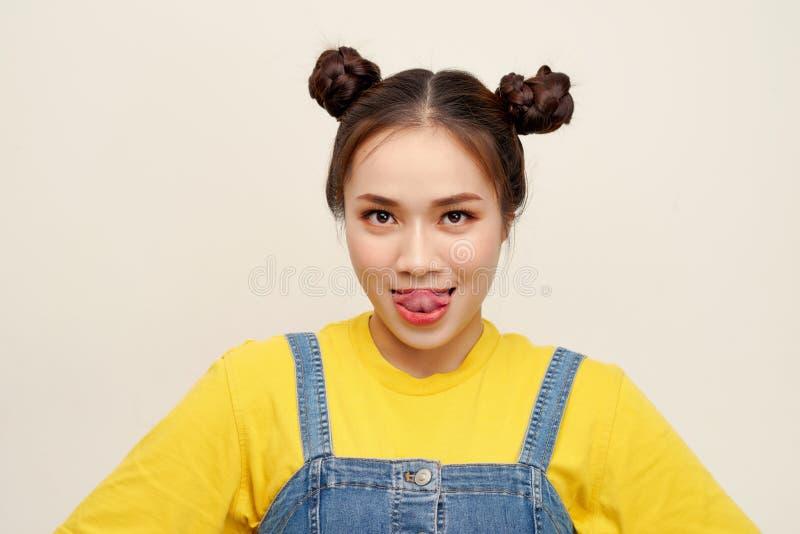 Dungaree джинсов красивой молодой азиатской девушки нося с волосами 2 плюшек на белой предпосылке стоковые изображения