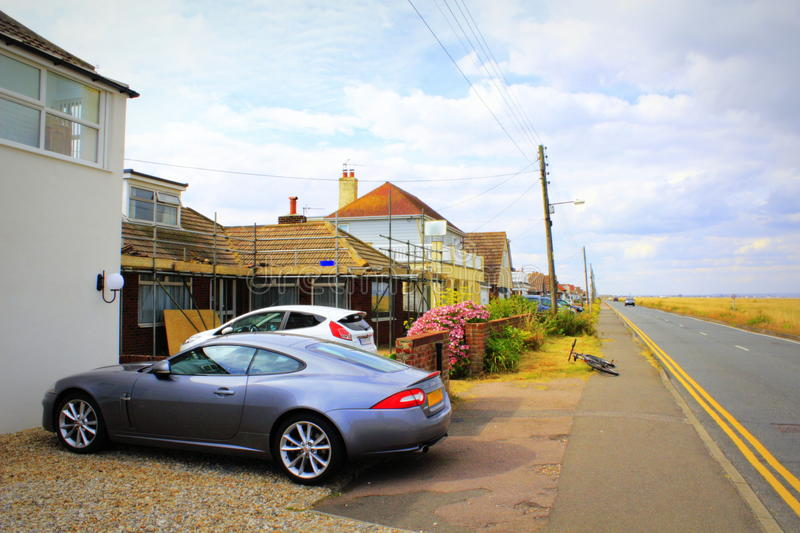 Dungeness coastal road Lydd-on-Sea United Kingdom. Dungeness coastal road and roadside houses of Lydd-on-Sea village.Lydd-on-Sea is a modern village, mostly stock image