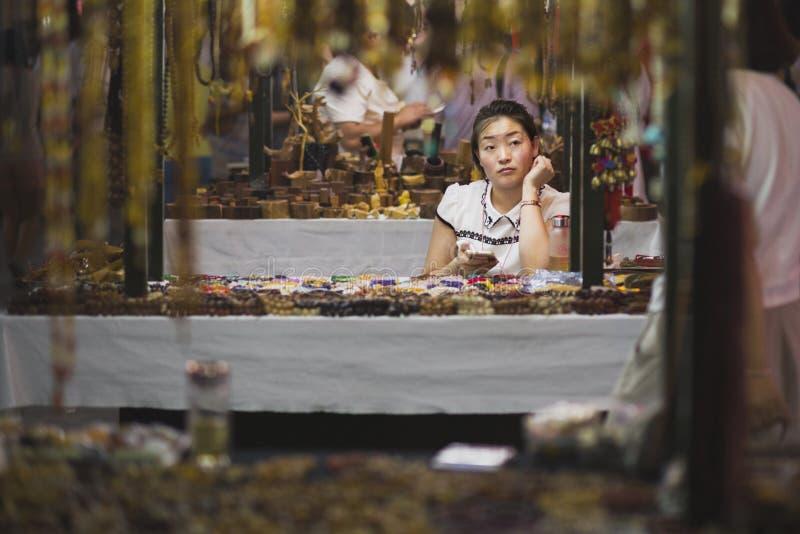 Dunhuang, Chiny - 08 06 2016: Chińczyk rzemieślniczki sprzedawania pamiątki przy Shazhou rynkiem, noc rynek w Dunhuang zdjęcia royalty free