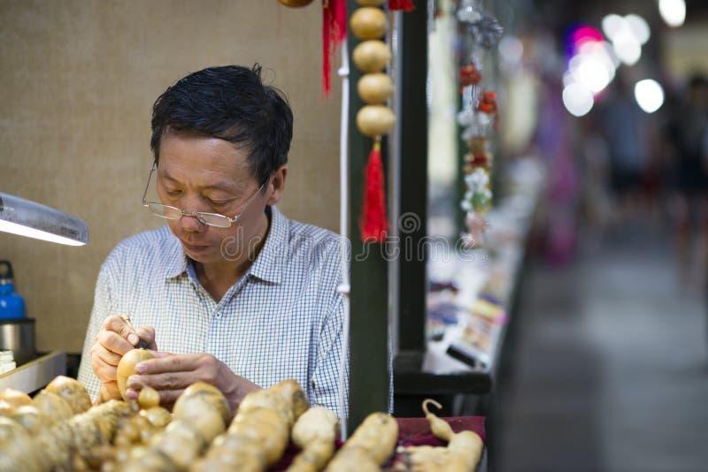 Dunhuang, Chiny - 08 06 2016: Chińczyka rzemieślnika sprzedawania pamiątki i drewniane rzeźby przy Shazhou rynkiem, noc rynek obraz stock