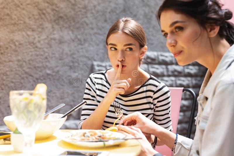 Dunkeläugige stilvolle Frau, die geheim Tischbesteck vom Restaurant stiehlt stockfotos