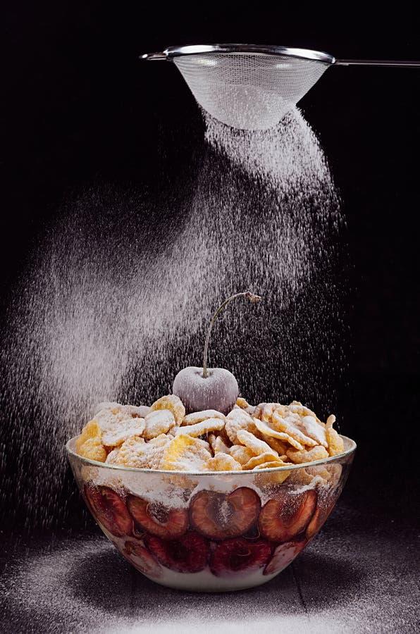 Dunkel vervollkommnen Sie raffinierten Nachtisch mit reifer Kirsche und bewegen Sie fallenden Puderzucker wellenartig stockbild