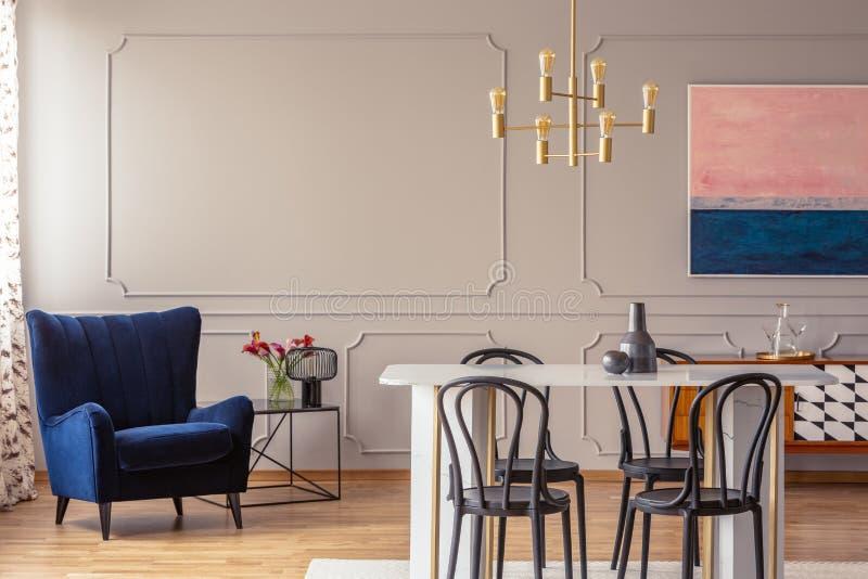 Dunkelblauer Lehnsessel in einem Esszimmerinnenraum mit einer Tabelle, Stühlen und einer goldenen Lampe stockfotos