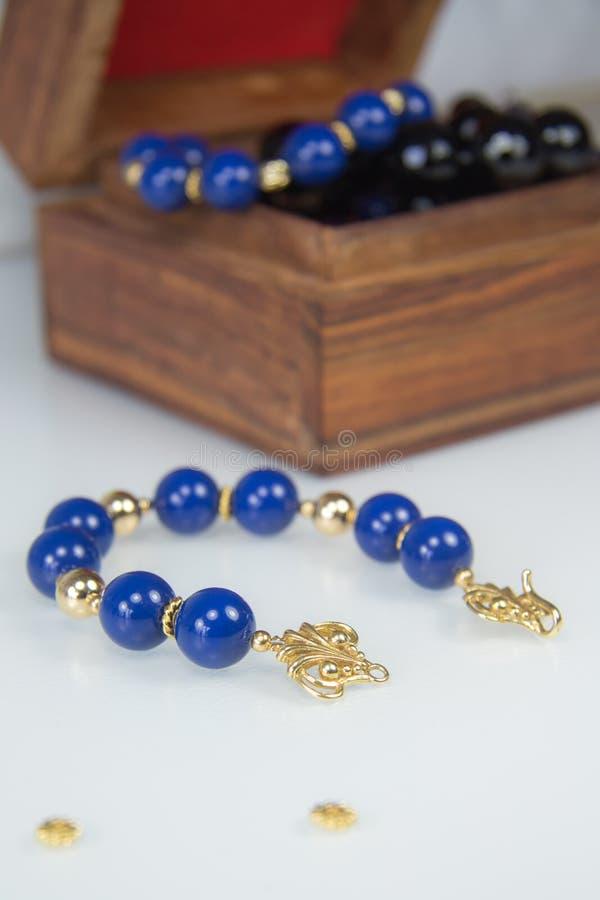 Dunkelblaues perlenbesetztes Armband mit Goldverschluß lizenzfreie stockfotos
