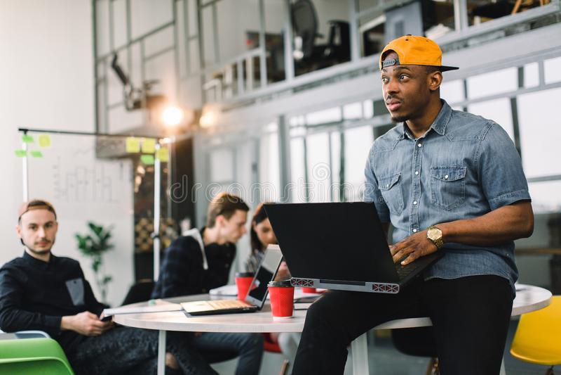 Dunkelhäutiger Afroamerikanermitarbeiter im Jeanshemd und in der gelben Kappe und im mit Laptop im modernen Büro gemischtrassig stockbilder
