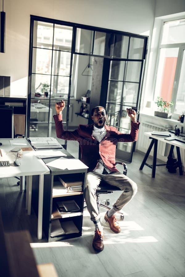 Dunkelhäutiger Geschäftsmann, der nachdem den ganzen Tag arbeiten gähnt lizenzfreie stockfotos