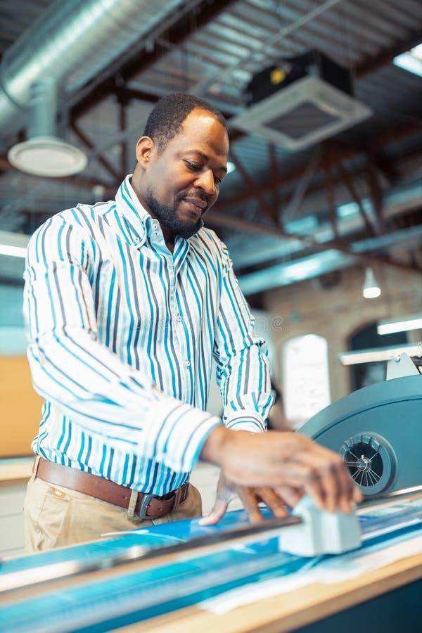 Dunkelhäutiger Mann, der schwer in der Papierherstellung arbeitet stockfotografie