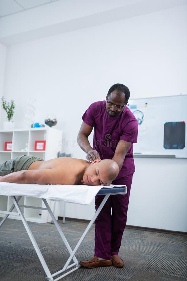 Dunkelhäutiger Massagetherapeut, der Körper des Sportlers massiert lizenzfreies stockfoto