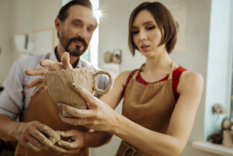 Dunkelhaarige Berufsceramists, die große Teeschale halten lizenzfreie stockfotos
