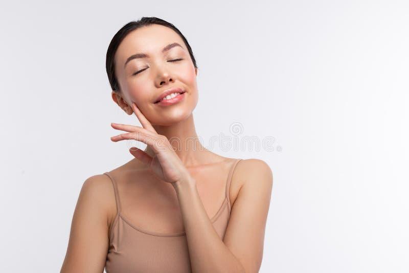 Dunkelhaarige Frau, die das beige Unterhemd schlie?t ihre Augen tr?gt lizenzfreie stockbilder