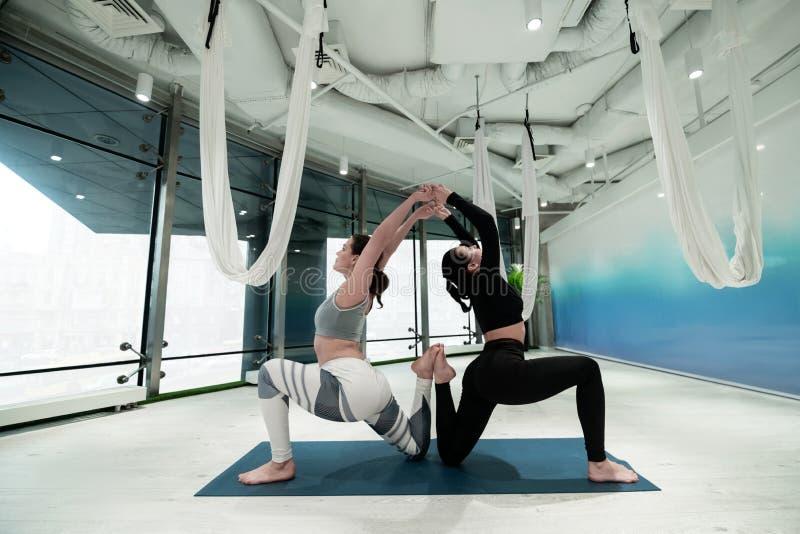 Dunkelhaarige Schwestern, die ihre Rückseiten beim Yoga zusammen tun ausdehnen lizenzfreies stockfoto