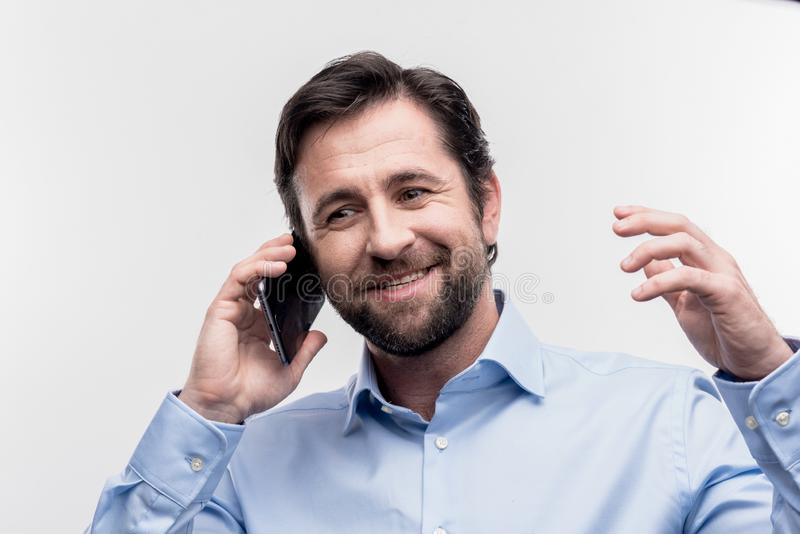 Dunkelhaariger bärtiger Geschäftsmann, der seinen Teilhaber anruft lizenzfreie stockbilder