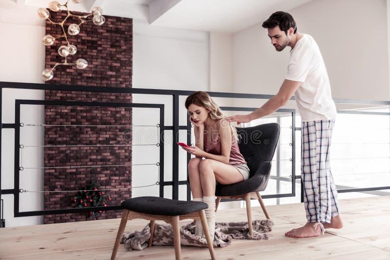 Dunkelhaariger bärtiger junger Mann in einem weißen T-Shirt fragend seine Frau nach etwas stockbild