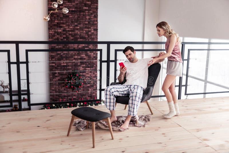 Dunkelhaariger bärtiger junger Mann in einem weißen T-Shirt und in seiner Frau, die ausdrucksvoll schaut lizenzfreie stockfotografie