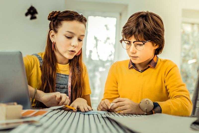 Dunkelhaariger Bruder und Kinder, die Aufgabe für Entwurfsschule durchführen stockfotos
