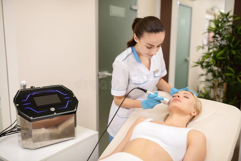 Dunkelhaariger Dermatologe, der Laser-Hautbehandlung f?r Kunden tut lizenzfreies stockbild