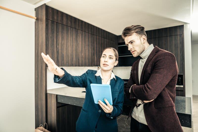 Dunkelhaariger Grundstücksmakler, der blaue Tablette bei der Konsultierung des Geschäftsmannes hält lizenzfreie stockbilder