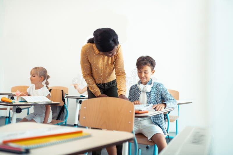 Dunkelhaariger lächelnder Junge beim Sprechen mit Lehrer stockfotos