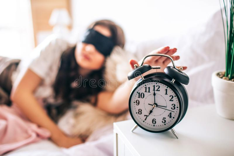 Dunkelhaariger schöner junger Brunette in ihrem Bett aufwachen Schläfrige Frau in der schwarzen Maske, die Hand erreicht, um abzu stockfoto