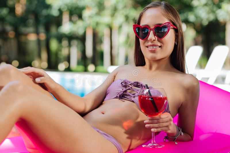 Dunkelhaariger vorbildlicher tragender Schwimmenanzug, der Cocktail hält lizenzfreie stockbilder