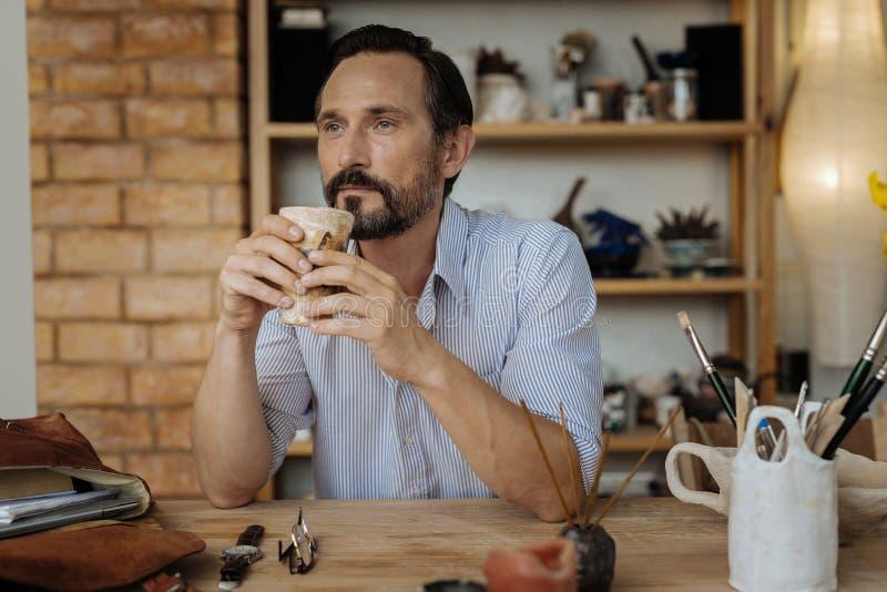 Dunkelhaariges handicraftsman, das geschmackvollen schwarzen Kaffee trinkt lizenzfreie stockbilder