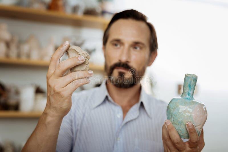 Dunkelhaariges handicraftsman, das Handvoll Töpferware hält lizenzfreie stockfotos