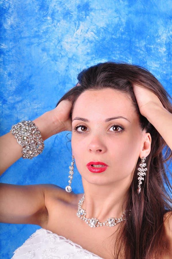 Dunkelhaariges Mädchen in den exclavant Ohrringen und in einer Halskette auf einem abstrakten Hintergrund stockbild
