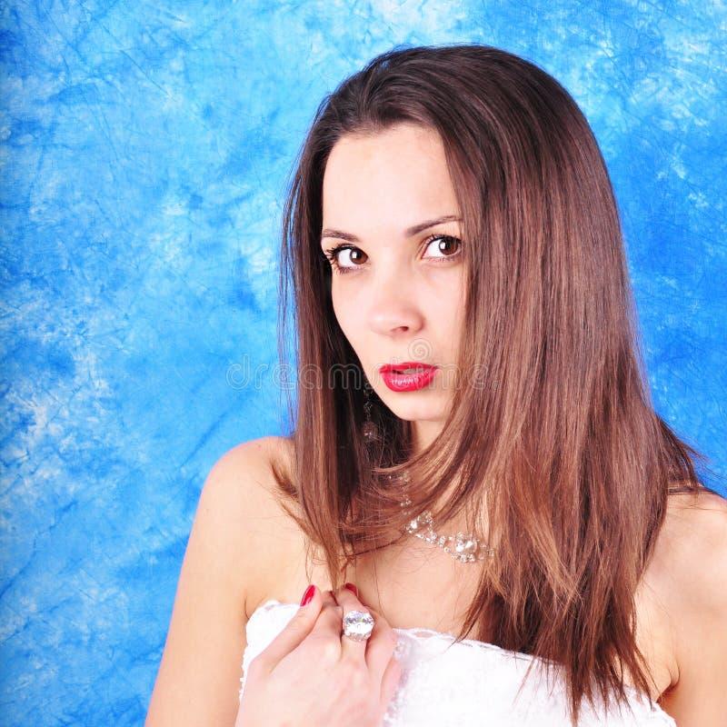 Dunkelhaariges Mädchen in den exclavant Ohrringen und in einer Halskette auf einem abstrakten Hintergrund stockfoto