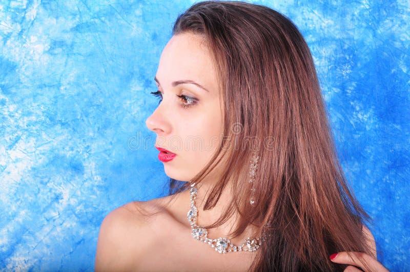 Dunkelhaariges Mädchen in den exclavant Ohrringen und in einer Halskette auf einem abstrakten Hintergrund lizenzfreies stockfoto