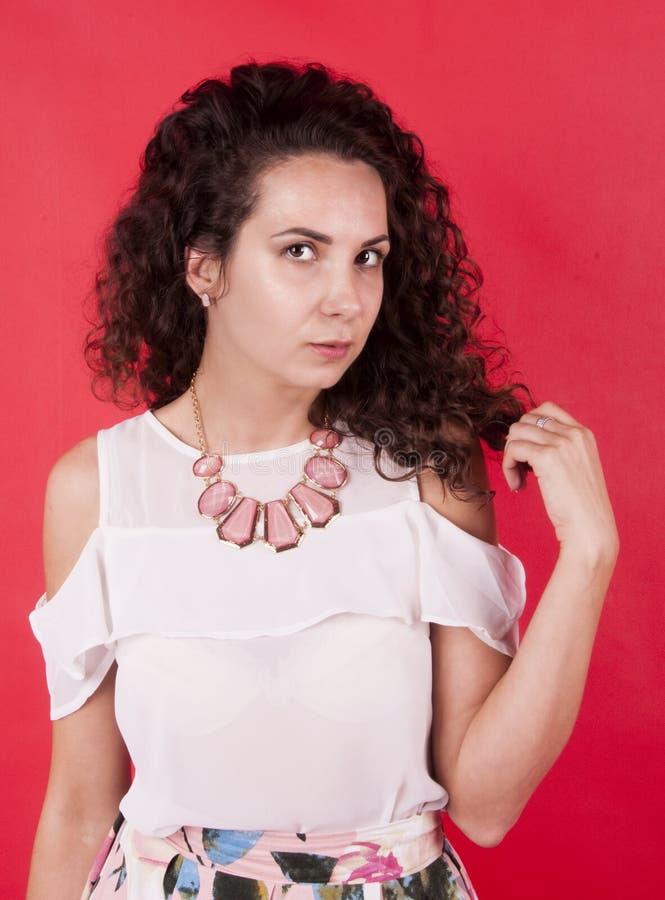 Dunkelhaariges Mädchen in der rosa Halskette auf rotem Hintergrund stockbild