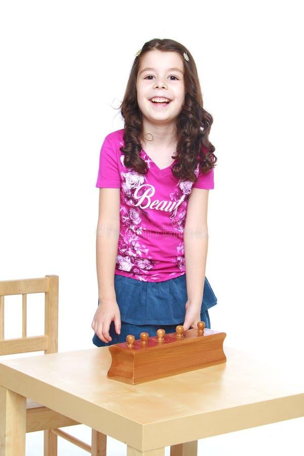 Dunkelhaariges Mädchen in einem Montessori-Kindergarten stockbild