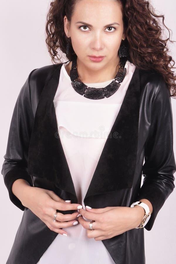 Dunkelhaariges Mädchen mit einer schwarzen Halskette auf einem weißen Hemd lizenzfreie stockfotografie