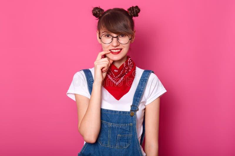 Dunkelhaariges Studentenlächeln, hält Vorderfinger auf ihrer Lippe, schaut schüchtern Junges Mädchen trägt T-Shirt, Denimoverall  lizenzfreie stockfotos