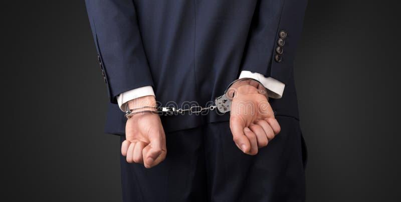 Dunkelheit backgrounded nah mit Handschellen gefesselter Mann lizenzfreie stockbilder