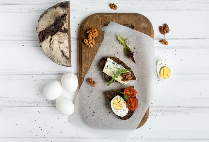 Dunkelheit schnitt Brot, Blauschimmelkäse, Eier auf dem hölzernen Schneidebrett, das mit Nüssen verziert wurde Flache Lage, Drauf stockbild
