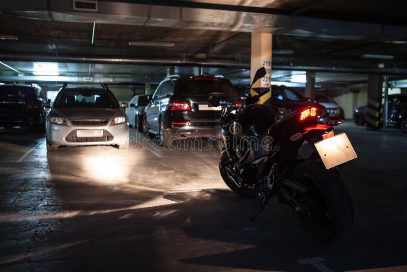 Dunkelheitsuntertageparkplatz mit schwarzem Motorrad mit Maschine und Licht einschalten stockfotos