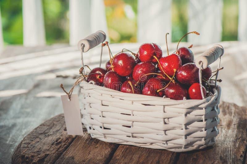 Dunkelrote reife große Kirschen in einem weißen Weidenkorb auf einem Holztisch, selektiver Fokus Abschluss oben stockbild