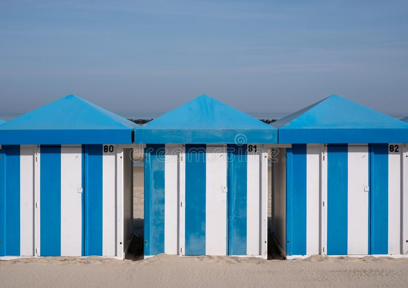 Dunkerque, France: Blue and white striped beach huts on the sand on the sea front at Malo-Les-Bains beach in Dunkirk. Photographed on a clear spring day stock photography
