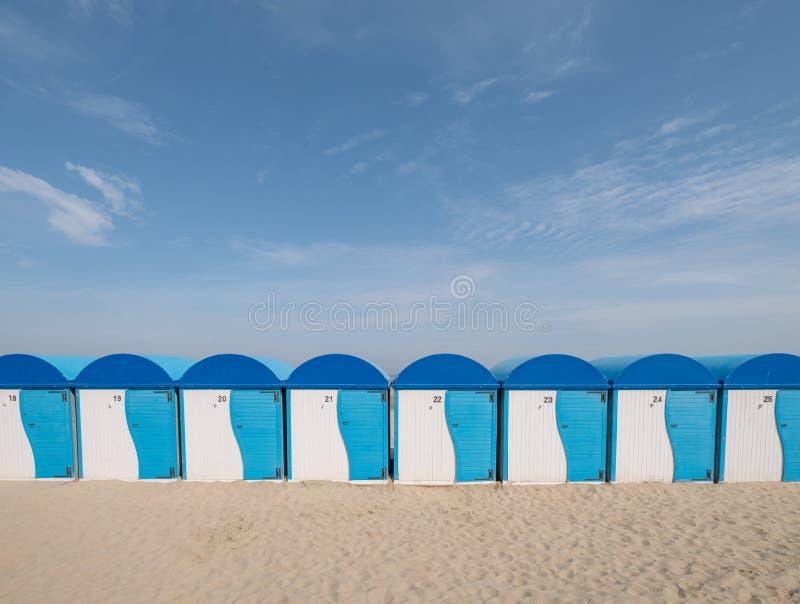 Dunkerque, Francja: Rz?d b??kitne i bia?e pasiaste pla?owe budy na dennym przodzie przy Les pla?? w Dunkirk obrazy stock