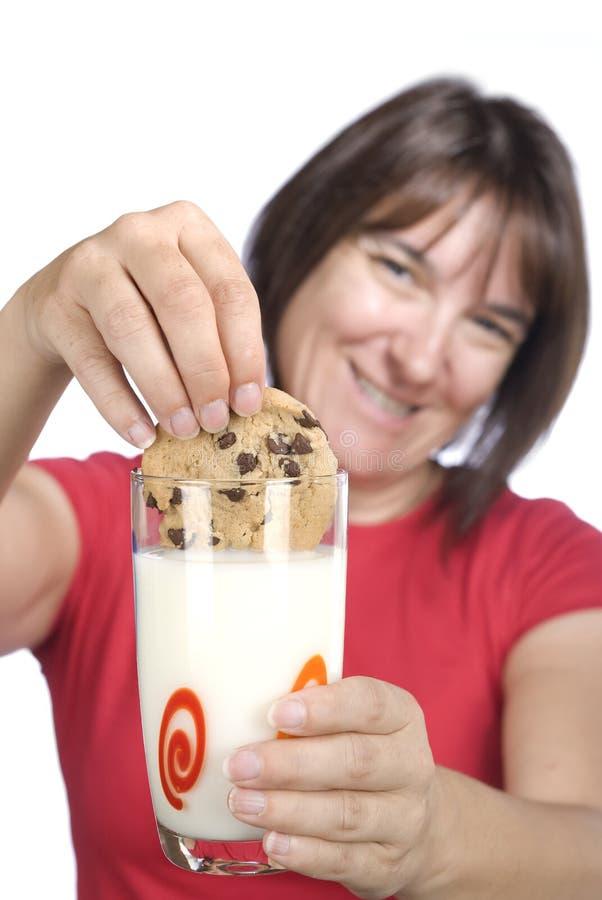 dunking för chipchokladkaka mjölkar kvinnan arkivfoto