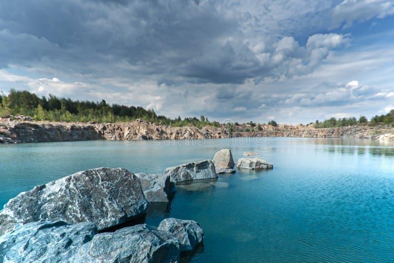 Dunkle drastische Landschaftsstürmischer Himmel über See mit Felsen See herein stockbilder