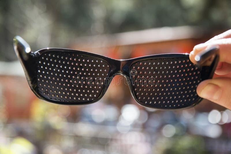 Dunkle Gläser mit kleinen Löchern lizenzfreie stockbilder