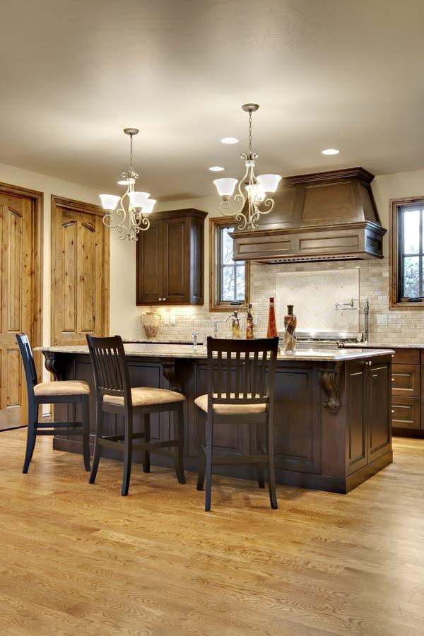 Dunkle hölzerne Küche mit Granit-Zählwerken stockbilder