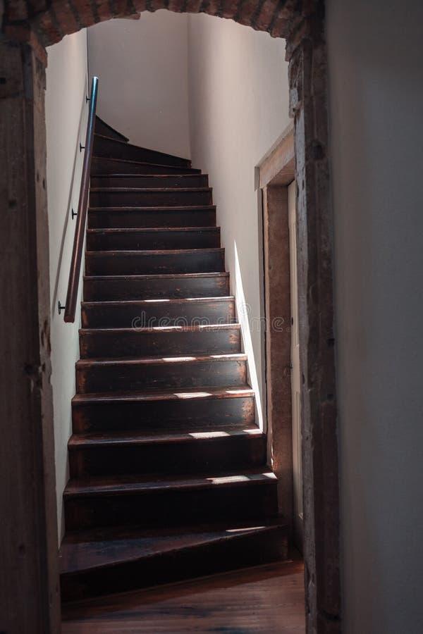 Dunkle Holztreppe in einem alten Haus Weiße verputzte Wände lizenzfreies stockbild