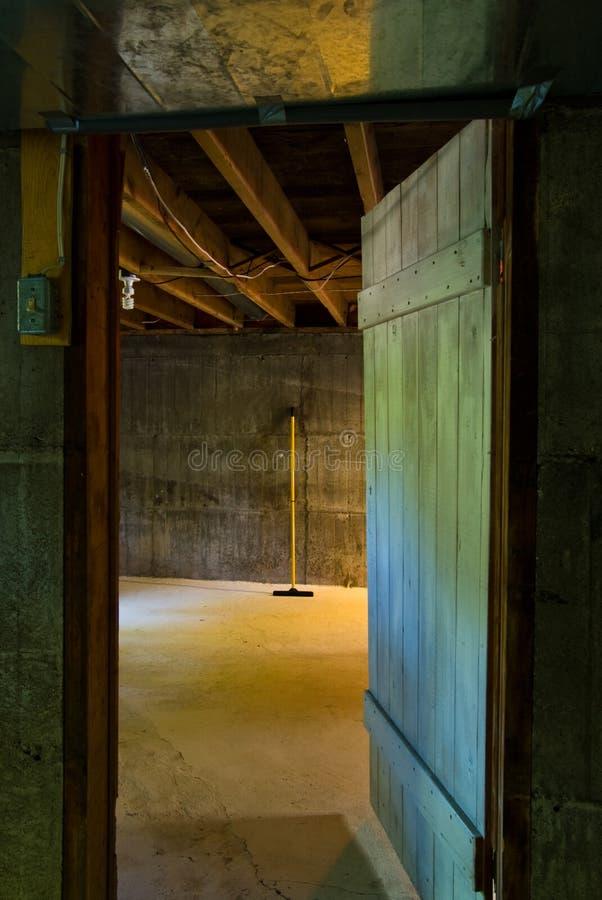 Dunkle Kellertür in Raum mit Mopp lizenzfreies stockfoto